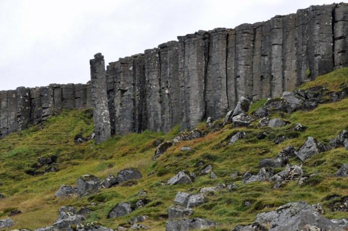 Dark grey basalt columns rise high above a bright green field strewn with boulders