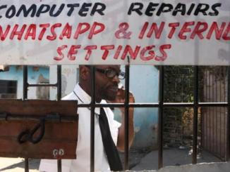 Norman Kazarire, 38, speaks on his mobile phone outside an internet shop in Epworth, east of the capital Harare, Zimbabwe, August 11, 2016. REUTERS/Philimon Bulawayo