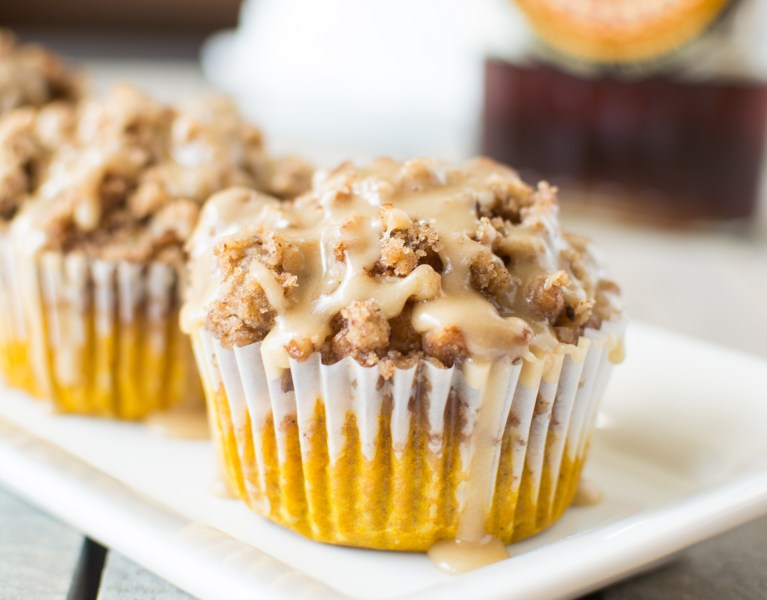 Moist and fluffy muffins loaded with pumpkin and autumn spices, piled high with a buttery streusel crumble, and drizzled with a thick maple glaze!