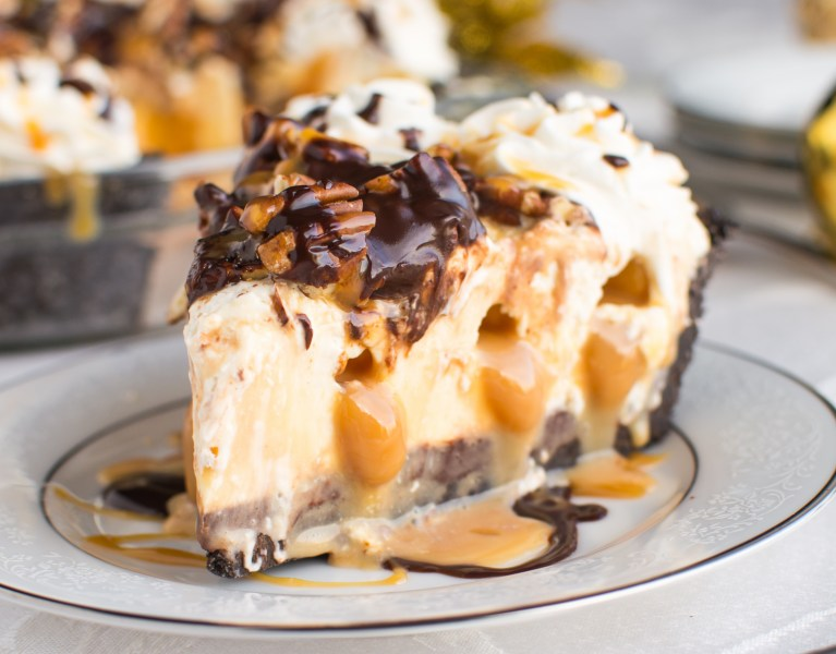 An Oreo cookie crust filled with a layer of dark chocolate ganache, a no-bake cheesecake-like filling INJECTED with pockets of caramel, and topped with caramel, ganache, and chopped pecans!