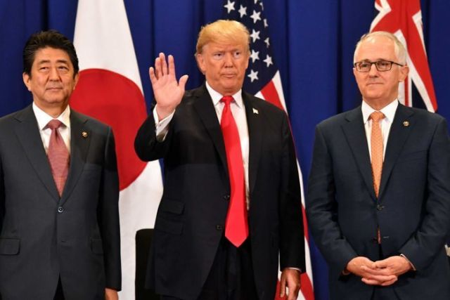 Shinzo Abe glances sideways while Donald Trump waves and Malcolm Turnbull looks dead ahead.