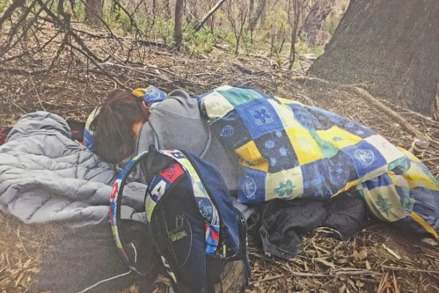 A woman appears to sleep under a blanket in bushland.