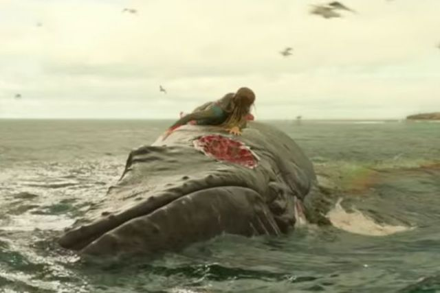 Actor on a whale in the ocean.
