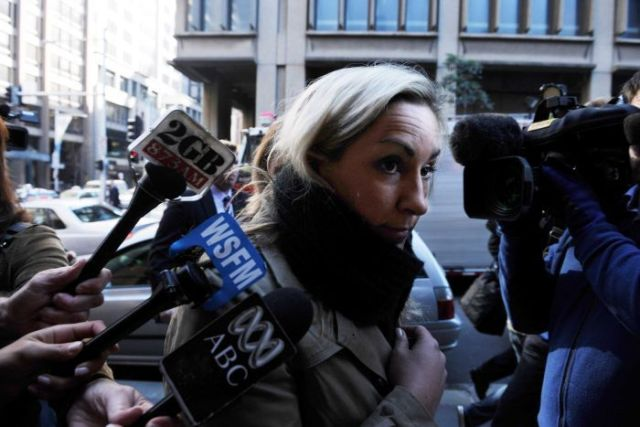 A blonde woman faces a press pack