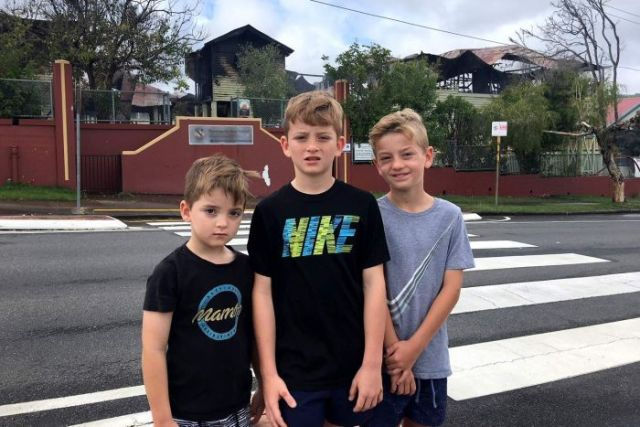 Three primary school-aged boys stand outside their school with fire-damaged buildings in background.