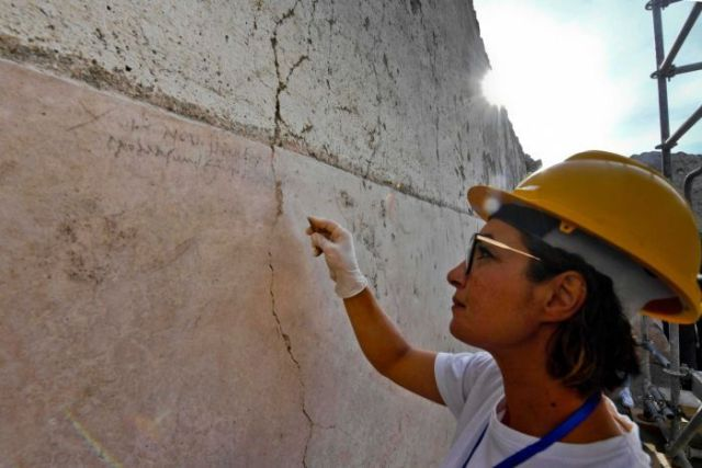 An archaeologist checks inscriptions on a wall during new excavations at the Pompeii archaeological site.