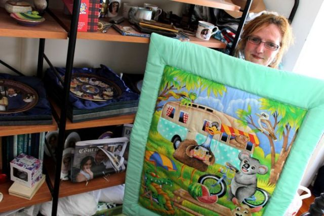 Woman stands holding quilt containing cartoon images of emu, koala and kangaroo.