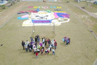 Staff, students and artists at Hujing Elementary School with a newly created cat mural using recycled materials.