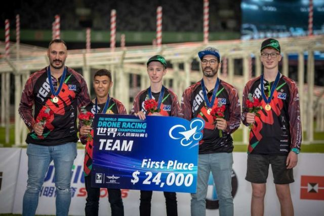 The Australian team at the podium at the World Drone Racing Championships in Shenzhen. They are holding a US$24,000 cheque.