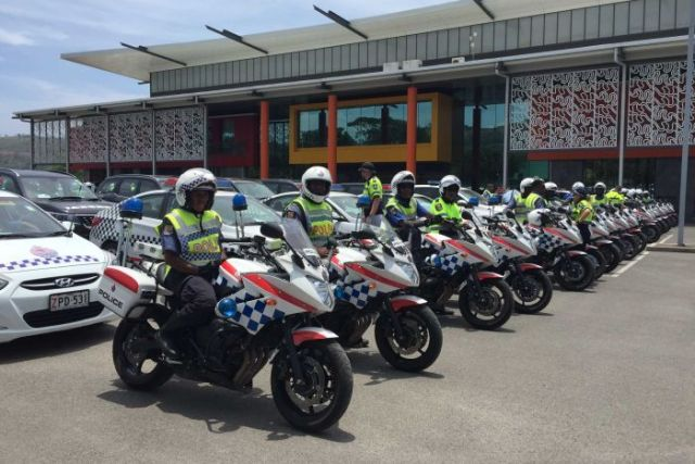 police on police motorbikes line up in a row outside a building