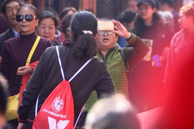 a man holds a phone up to capture footage as a crowd of people surround him