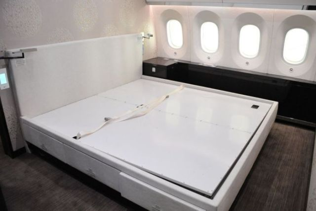 A white bed with a headboard inside a plane, with plane windows running next to it