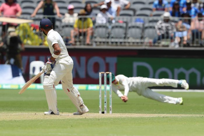 Virat Kohli watches Peter Handscomb dive to catch him out in the slips