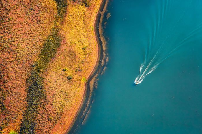 An aerial view of a boat whizzing across a lake.
