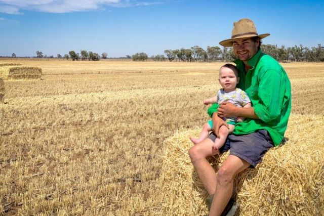 Farmer Cam Parker sitting on a hay bale with his toddler son Freddie.