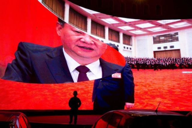 A child stands near a large screen showing photos of Chinese President Xi in China's Xinjiang region.