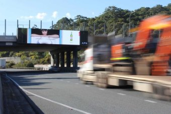 A truck passes under a large electronic billboard on the M1 at Tugun.