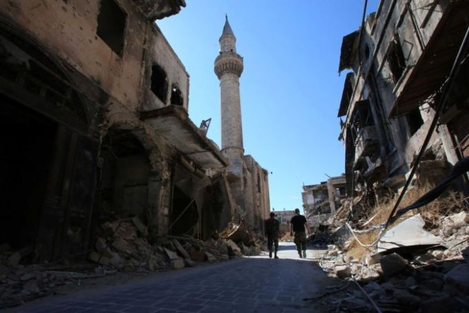 Syrian government soldiers walk in the damaged al-Farafira souk in the government-held side of Aleppo.
