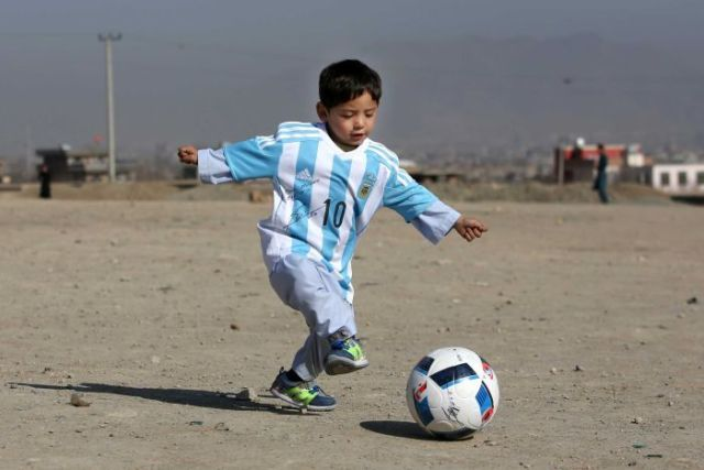 Afghan boy Murtaza Ahmadi plays with a ball in Kabul while wearing a shirt signed by Lionel Messi.