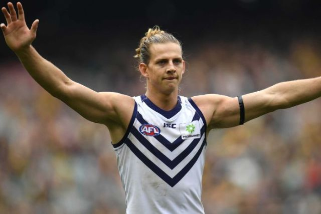 A mid shot of Fremantle Dockers captain Nat Fyfe standing with his arms outstretched in a white jersey.