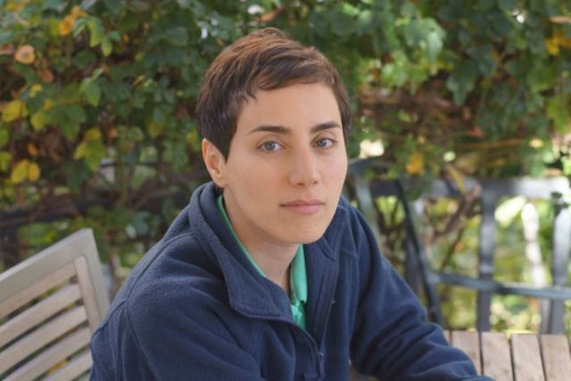 Maryam Mirzakhani seated on a bench in a garden setting.