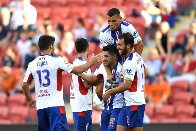 Jets players celebrate a goal against Brisbane