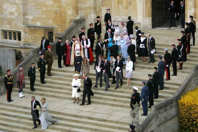 Britain's Prince Charles and the Duchess of Cornwall walk from St George's Chapel and followed by a crowd.