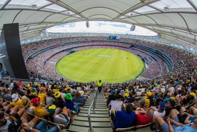 A wide shot from the top of the Perth Stadium stands showing a near-capacity crowd watching a cricket match.