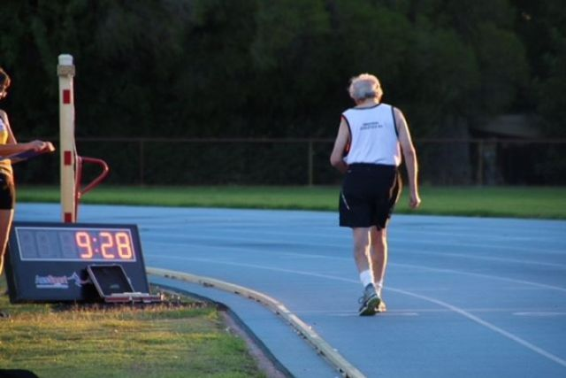 An elderly man on a blue running track next to a timing clock.