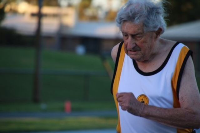 An elderly man runs in a running singlet in the early morning light.