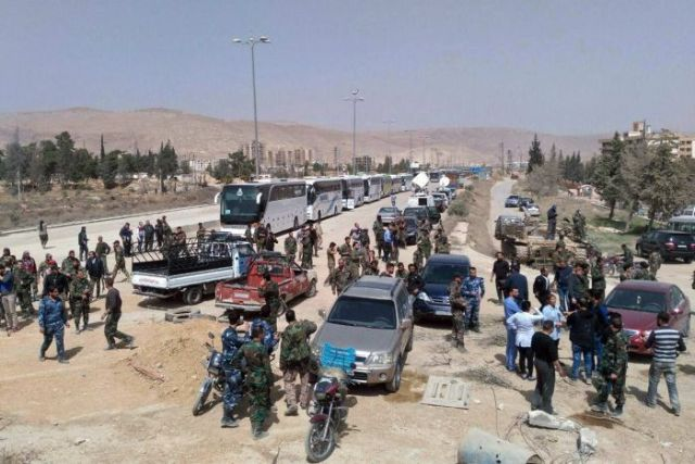 Syrian government forces oversee the evacuation by buses of rebel fighters and their families.