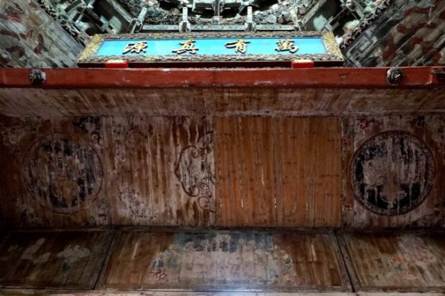 Photo looks up at ceiling of structure with ornate decorations, four Chinese characters and a mural that has been sanded back