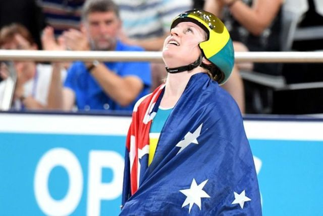 Morton, with the australian flag draped over her shoulders, looks to the roof of the stadium after her win