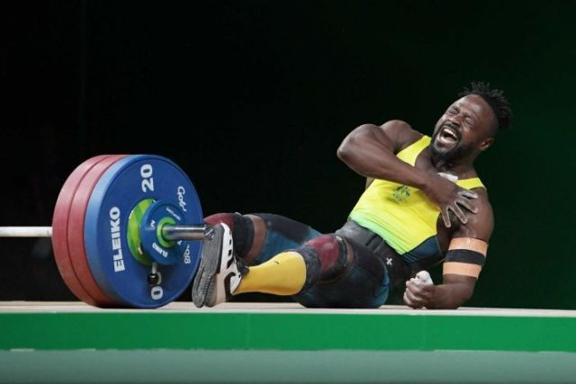 Weightlifter Francois Etoundi clutches his shoulder and falls to the ground
