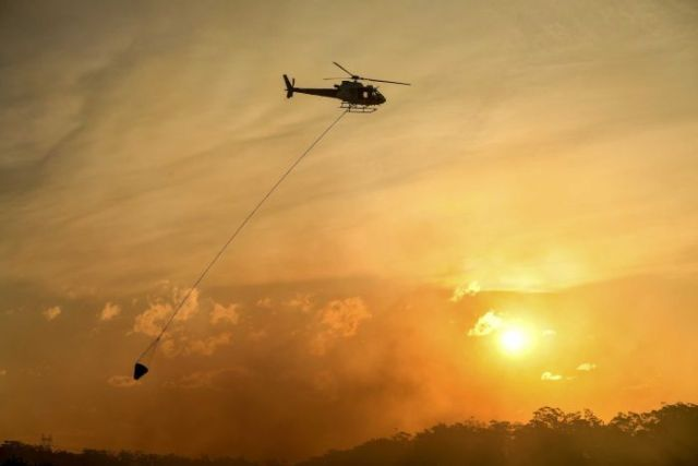 Helicopter water bombing a bushfire threatening homes in suburbs in Sydney's south-west on Sunday April 15, 2018.