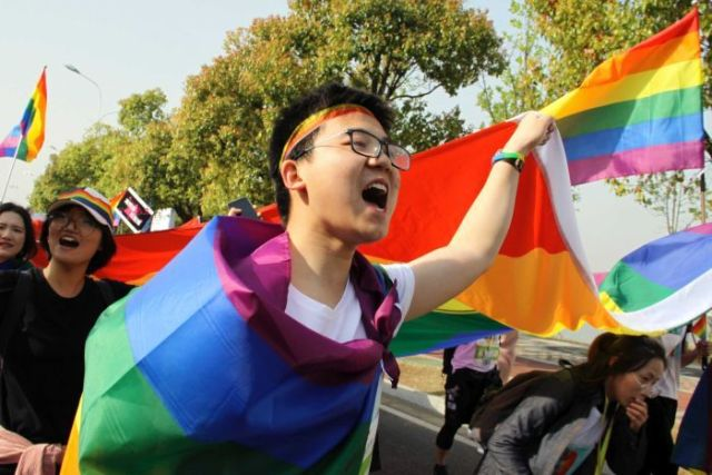 Young people wearing the rainbow flags are walking on the street of Nanjing city.