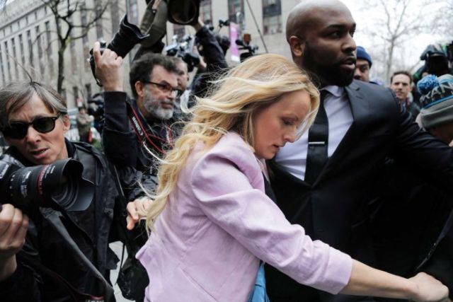 Stormy Daniels walks through a media pack with her head down, with the help of a man in a suit.