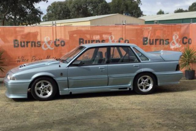 A boxy 1988 VL Commodore Walkinshaw Group in Panorama Silver parked at an auction lot.