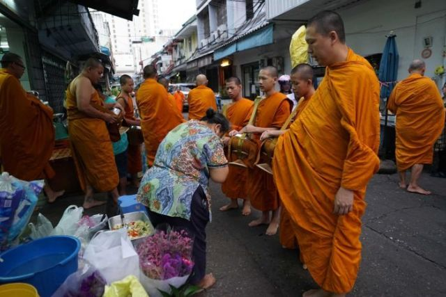 A woman bows to a group of men with shaved heads and dressed in saffron robes