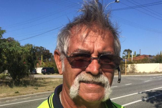 Thornlie resident Dirk Jagers in a yellow fluro top stands on the street, with powerlines and sky in the background.