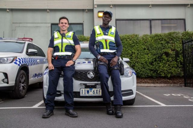 Senior Constable Scott Allison and Constable Kur Thiek standing in front of a police car.