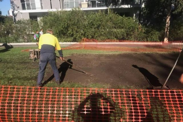 Council workers smooth-out dirt where concrete slab used to be