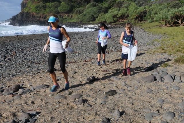 Runners pick up rubbish on a beach in northern NSW.