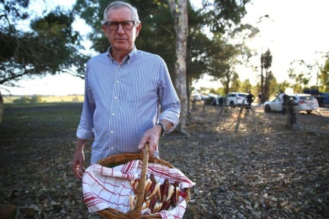 Neil stands holding a basket of sausages wrapped in bread.