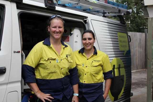 Two female electricians in blue and yellow workwear standing in front of a white van.