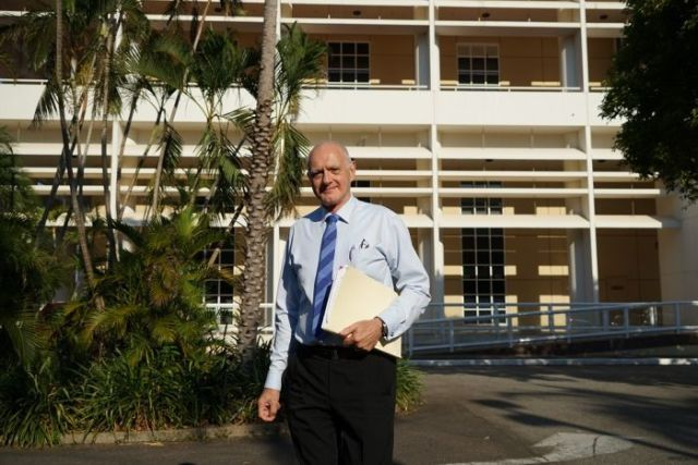 Len Notaras stands outside near palm trees, clutching a folder