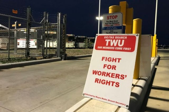 A sign, display the words 'FIGHT FOR WORKERS' RIGHTS', sits next to an open boom gate in front of parked buses.