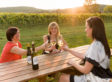 Image of three women drinking wine at a beautiful winery.
