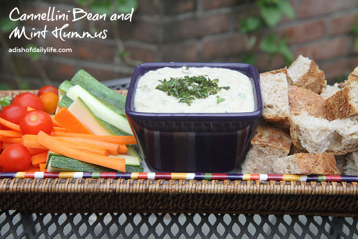 Cannellini Bean and Mint Hummus...an easy vegan appetizer recipe that takes minutes to make and will probably disappear in minutes too! If you're looking for something a bit healthier for tailgate season, this is it!