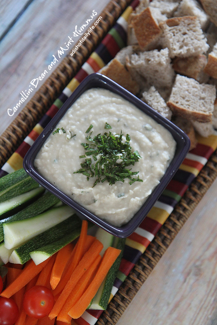 Cannellini Bean and Mint Hummus...an easy vegan appetizer dip recipe that takes minutes to make and will probably disappear in minutes too! If you're looking for something a bit healthier for tailgate season, this is it!